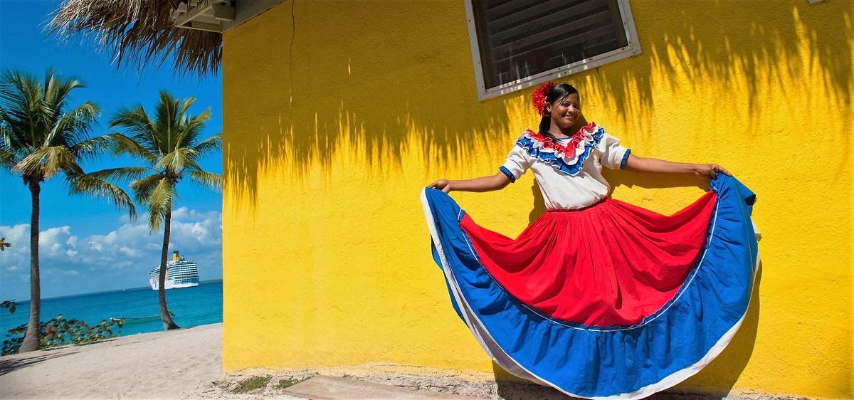 אשה בלבוש דומיניקני מסורתי רוקדת ליד בונגלו