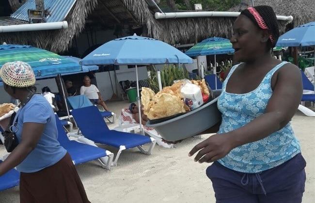 מלצרית בחופי בוקה צ'יקה מגישה אוכל דומיניקני לתיירים